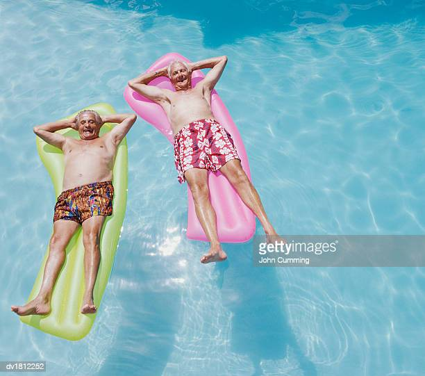 Two Senior Men Lying on Airbeds in a Swimming Pool