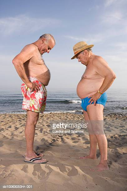 two senior men on beach, comparing abdomens, side view - fat guy on beach stock pictures, royalty-free photos & images