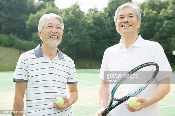 Two senior men on tennis court, holding racquets and balls, smiling