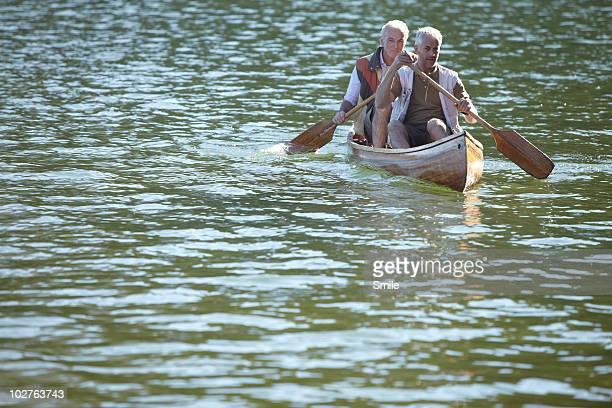 Two senior men paddling canoe on lake