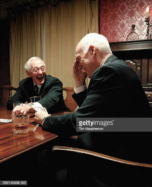 Two senior men playing cards at table, laughing