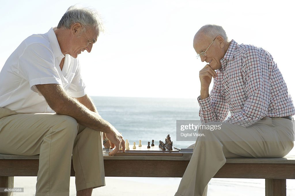 Two Senior Men Playing Chess, with the Sea in the Background : Stock Photo