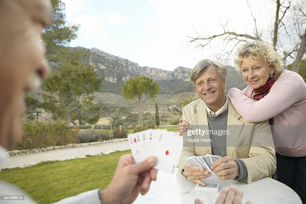 Two Senior Men Sit at a Table in the Countryside Playing a Card Game, Their Friend Watching : Stock Photo