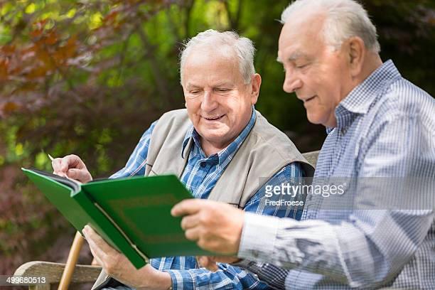 Two senior men sitting on bench in the park