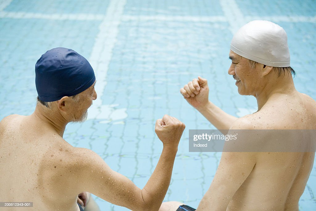 Two senior men sitting on edge of swimming pool, clenching fists : ストックフォト