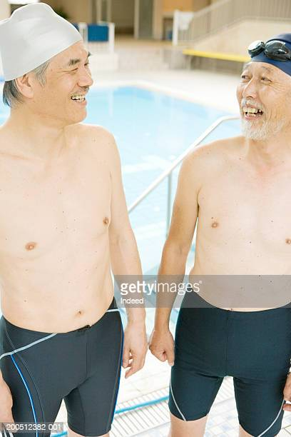 Two senior men standing beside swimming pool, smiling, elevated view