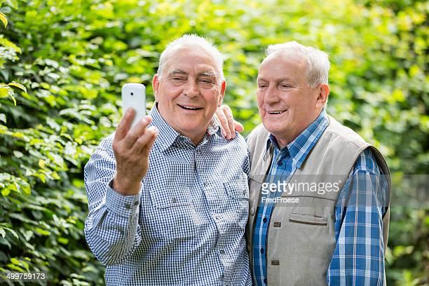 Two senior men taking selfie portrait with smart phone