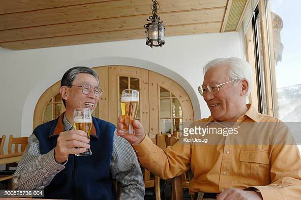 Two senior men toasting with beer, laughing