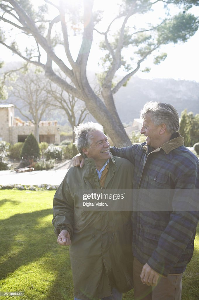 Two Senior Men Walk in the Garden With Their Arms Around Each Other, Talking and Smiling : Stock Photo