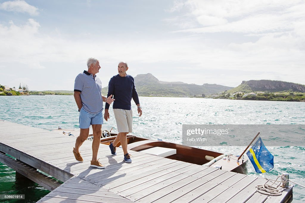 Two senior men walking on jetty : Stock Photo