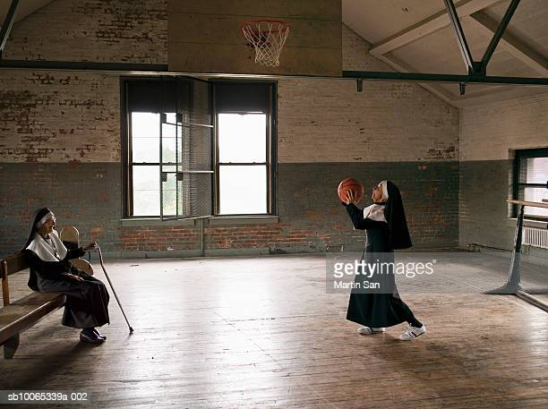 Two senior nuns in court, one throwing basket ball