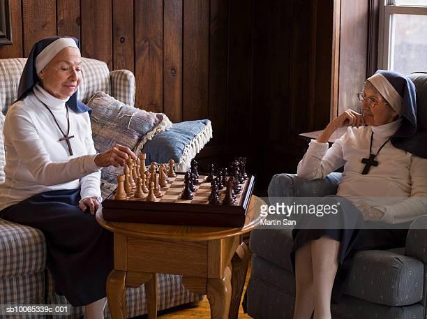 two senior nuns playing chess - 聖職服 ストックフォトと画像