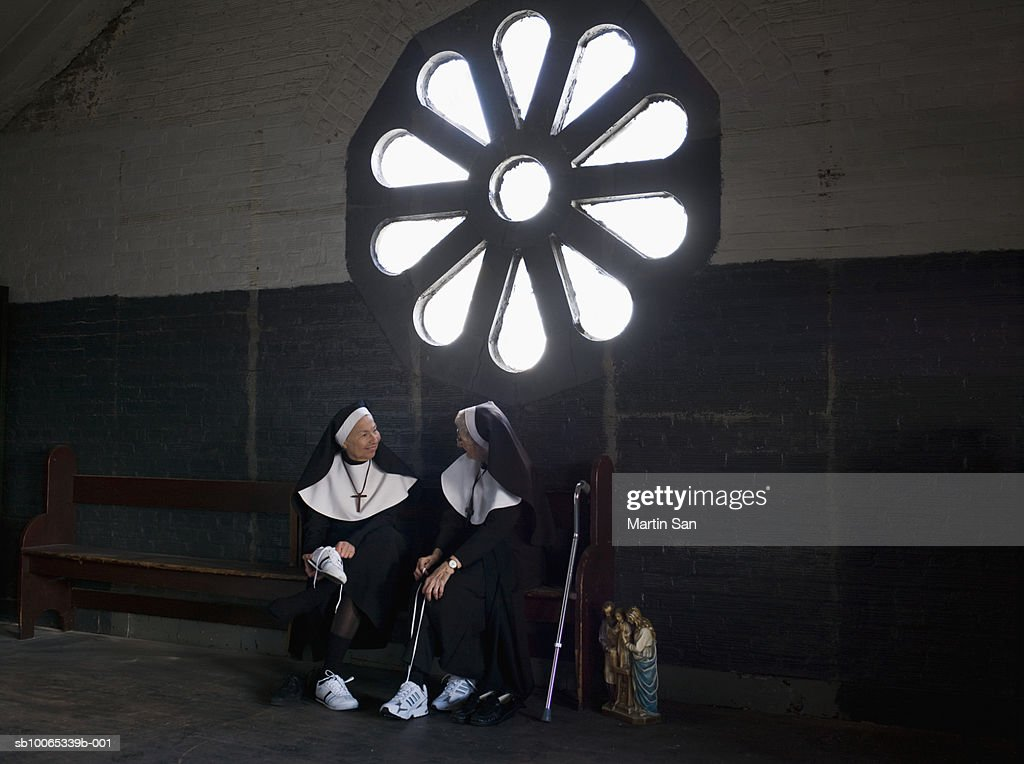 Two senior nuns sitting on bench talking and tying sneakers : Foto stock