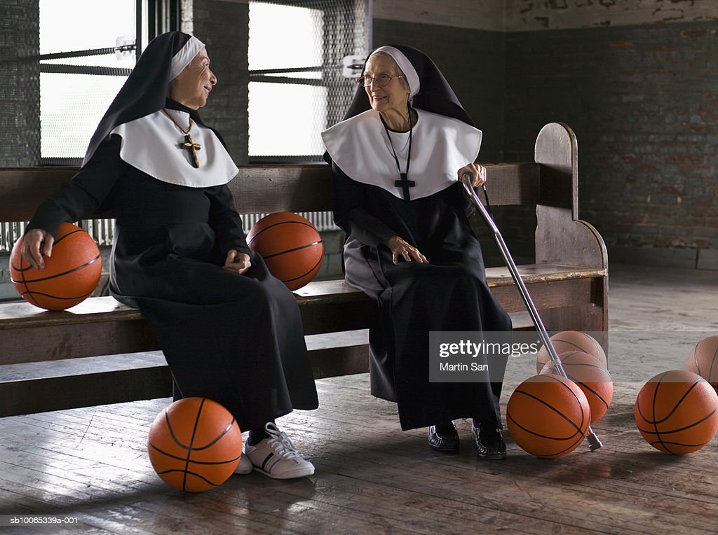 Two senior nuns sitting on bench with basketballs : Foto stock