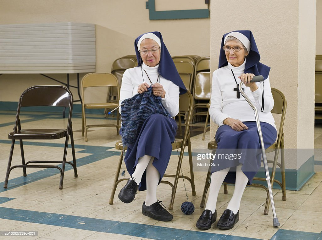 Two senior nuns sitting on chairs, one knitting, other looking away : Foto stock