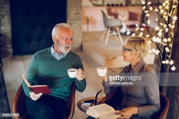 Deux personnes aînées, lire des livres tout en buvant le café à l'intérieur