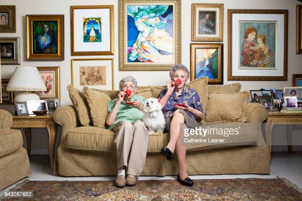 Two senior sisters drinking from red coffee cups with dog on sofa