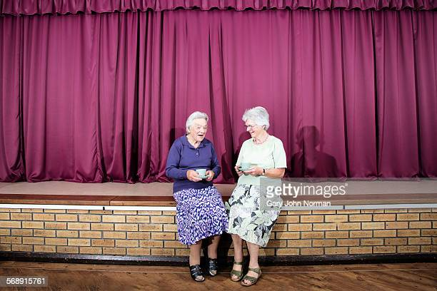 two senior sisters with cups of tea. - norman elder stock photos and pictures