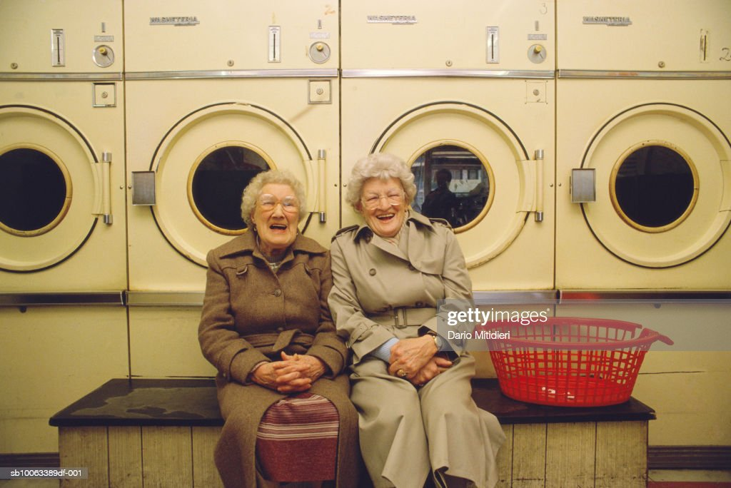 Two senior woman in launderettes, laughing, portrait