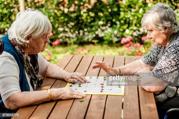two senior woman in the retirement community playing muehle game board - residential care stock photos and pictures