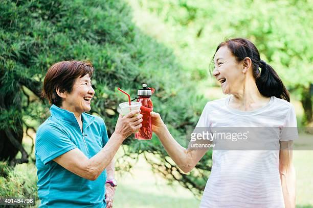 Two senior woman rehydrate after exercise, Yoyogi Park,Tokyo, Japan
