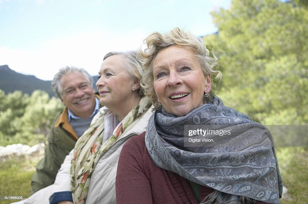Two Senior Women and a Man Sit Outdoors in the Countryside : Stock Photo