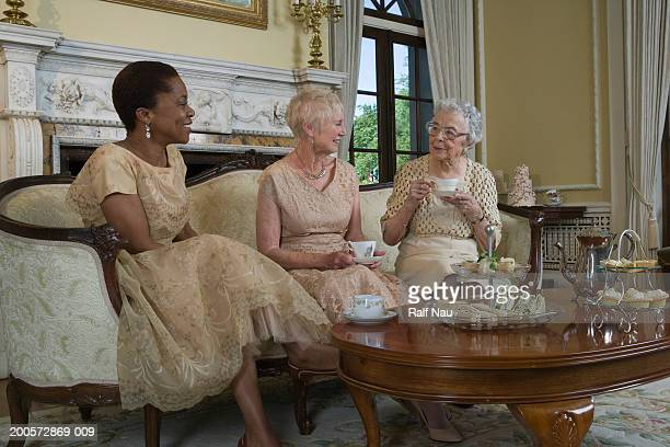 Two senior women and mature woman having tea
