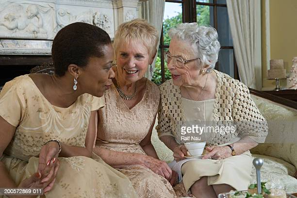 Two senior women and mature woman talking on sofa