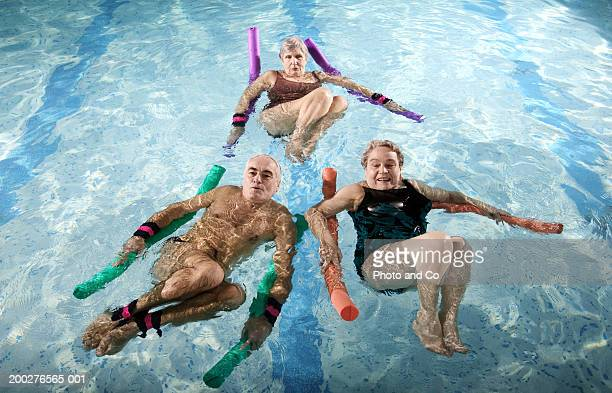 Two senior women and senior man using noodle floats in swimming pool