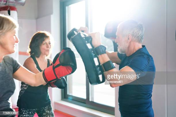 Two senior women boxing with their coach