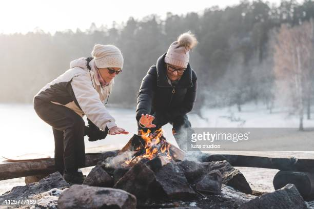 two senior women by a campfire in winter - older woman bending over stock pictures, royalty-free photos & images
