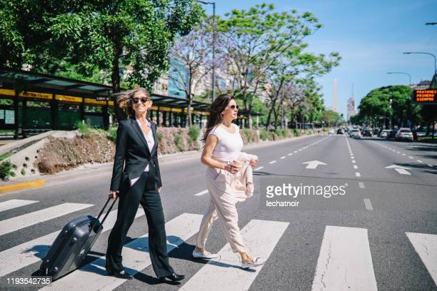 two senior women crossing a street in buenos aires - avenue stock pictures, royalty-free photos & images