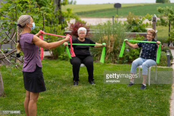 two senior women during healthy fitness training in garden with physical therapist wearing mask - retirement community stock pictures, royalty-free photos & images