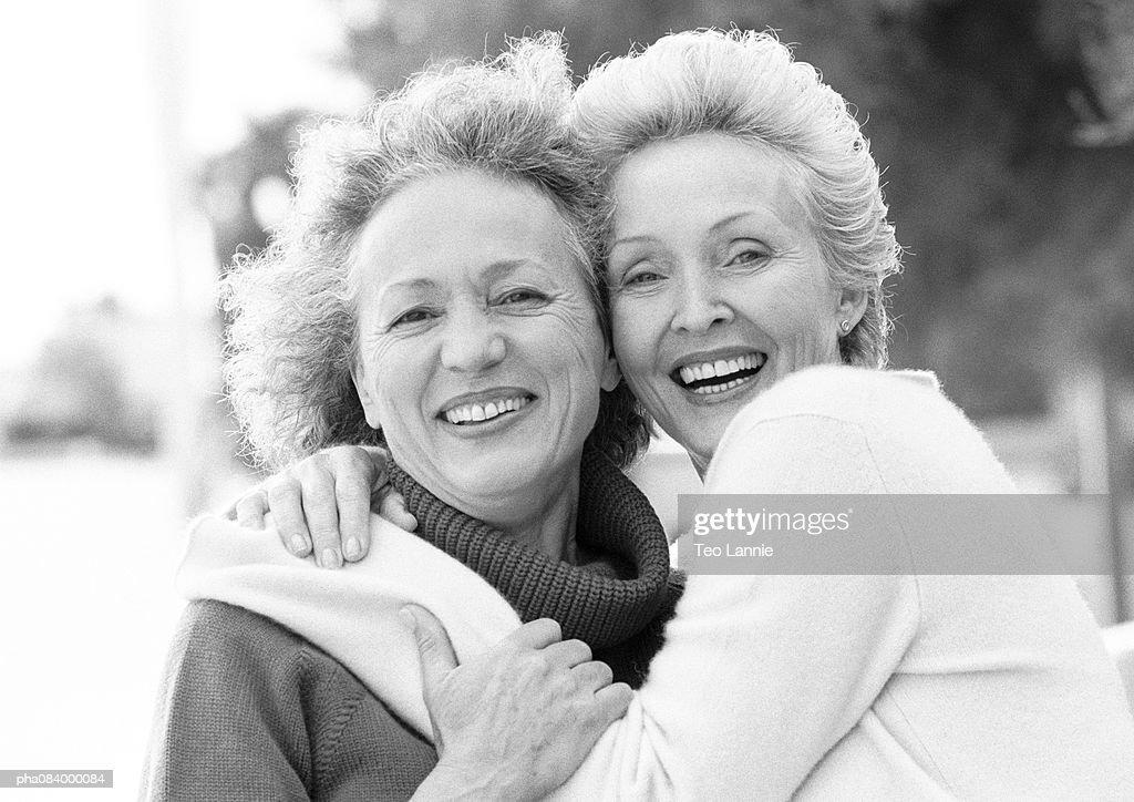 Two senior women embracing, smiling, portrait, B&W. : Stockfoto