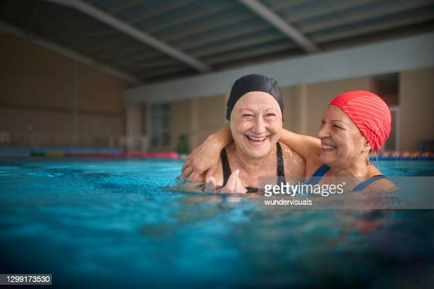 two senior women embracing together in swimming indoor pool - sporting term stock pictures, royalty-free photos & images