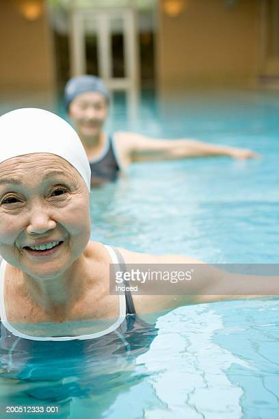 Two senior women exercising in swimming pool, smiling