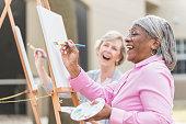 Two senior women having fun painting in art class