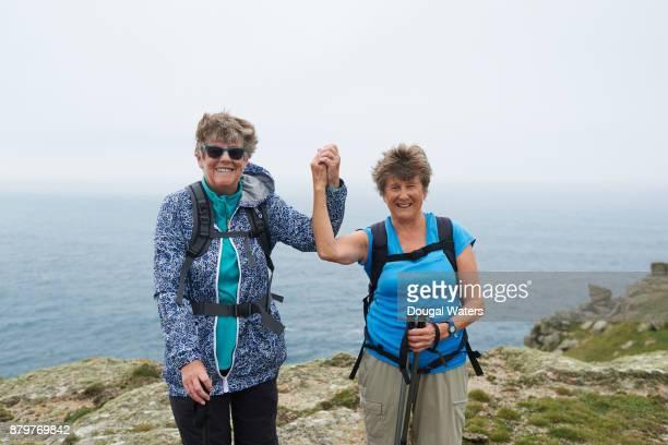 Two senior women hikers success on rocky coastline.