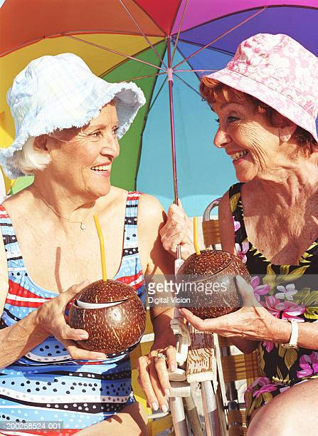 Two senior women holding coconuts, smiling at each other, close-up