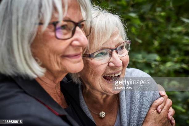two senior women hugging in garden - 70 79 years stock pictures, royalty-free photos & images