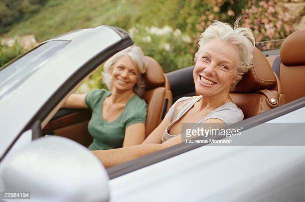 Two senior women in convertible car, smiling, portrait