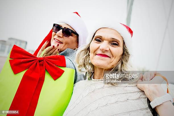 Two senior women in Santa hats on city street