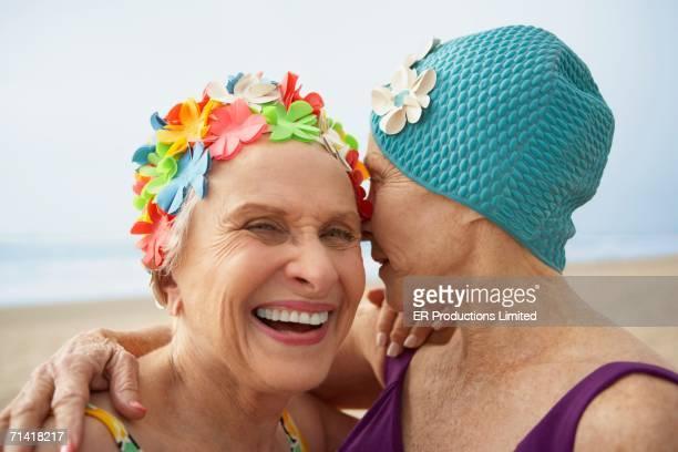 Two senior women in swim caps at the beach