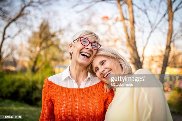 two senior women laughing at the park - friendship stock pictures, royalty-free photos & images