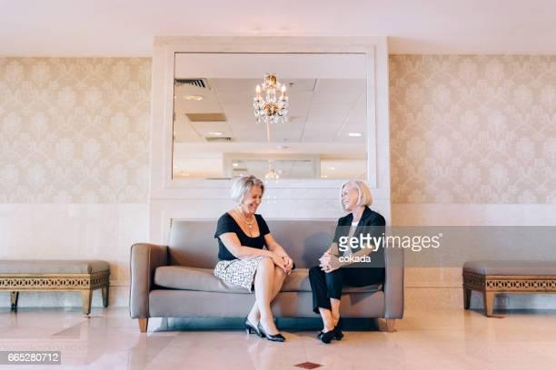 zwei frauen in führungspositionen in der hotellobby treffen - eingangshalle gebäudeteil stock-fotos und bilder
