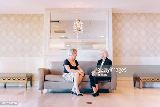 Zwei Frauen in Führungspositionen in der Hotellobby treffen