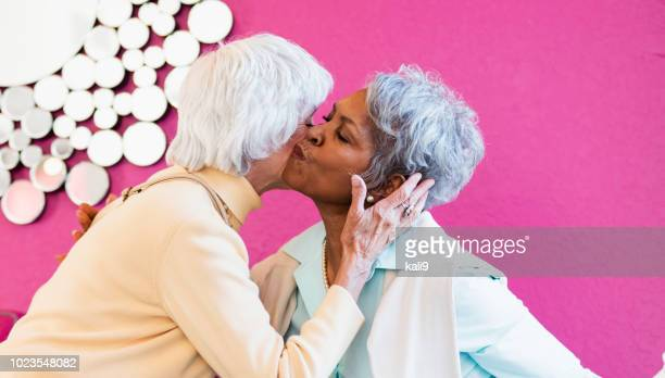 two senior women meeting in coffee shop - cheek stock pictures, royalty-free photos & images