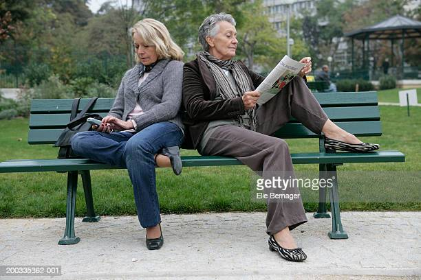 two senior women on park bench, one using mobile, one reading magazine - next to stock pictures, royalty-free photos & images