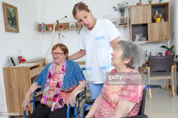 two senior women on wheelchairs and a nurse at the nursing home - residential care stock photos and pictures