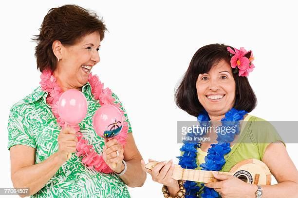 Two senior women playing ukulele and maracas